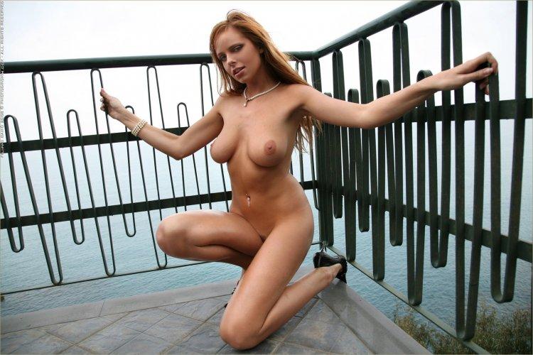 Красивая девушка нудистка позирует на пирсе