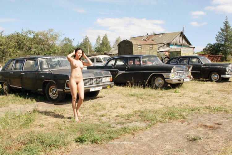 Обнаженная брюнетка позирует возле старых машин