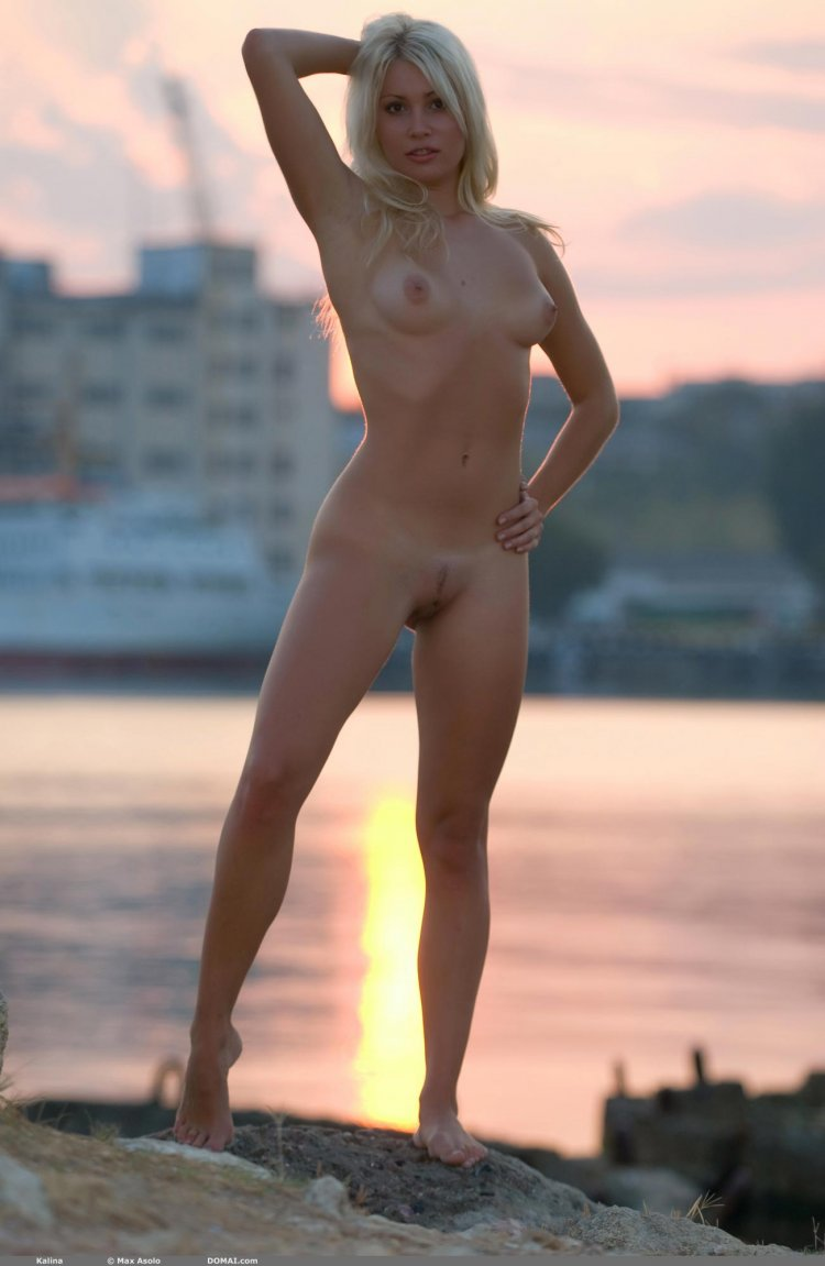 Красивая девушка позирует на берегу реки