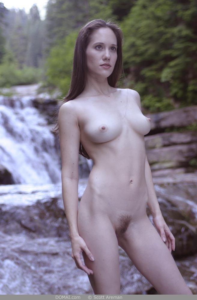 Голая сучка позирует возле водопада