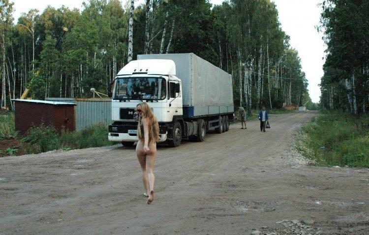 Веселая дама позирует возле большой фуры